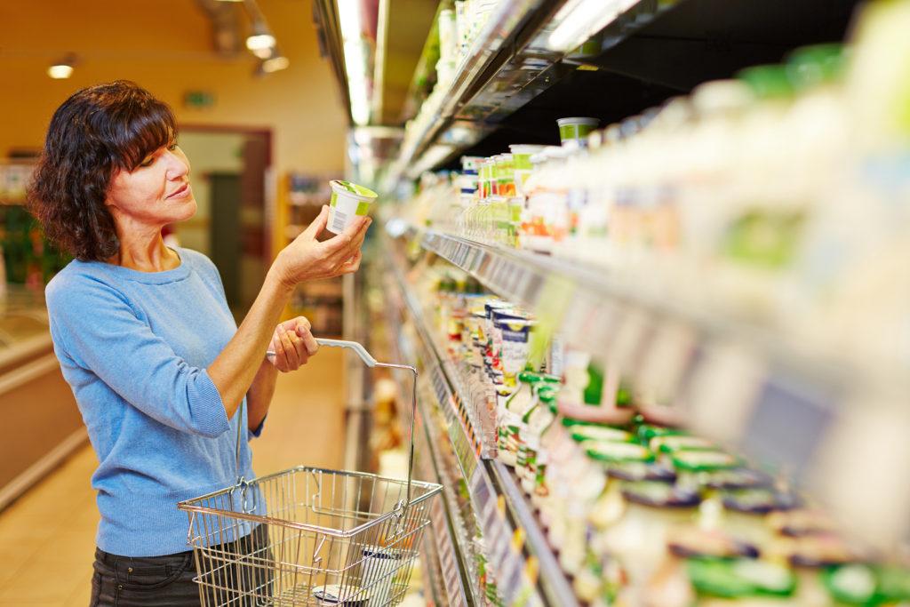 Elderly woman with shopping cart buying yogurt in supermarket